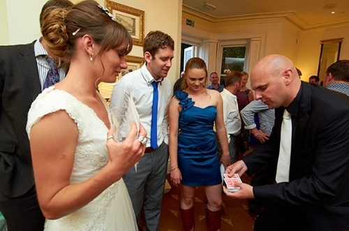 David performing magic to a bride and groom.